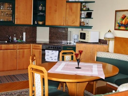 Küche mit Herd, Mikrowelle, Kaffeemaschine, Eßbereich mit Eckbank, Tisch und Stühle, auf dem Tisch ein Kerzenhalter,. (© Pöllmann)
