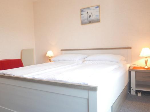 Schlafzimmer mit Doppelbett, Nachtkästchen mit Tischlampen, Tisch mit Stühlen. (© Ramsauer)