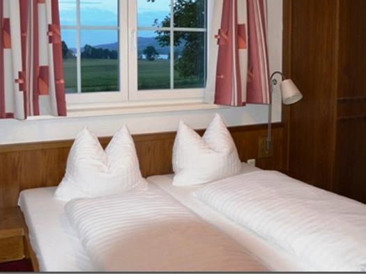 Schlafzimmer mit Doppelbett, Nachtkästchen mit Lampen, Tisch und Stühle, Kasten. (© Pöllmann)