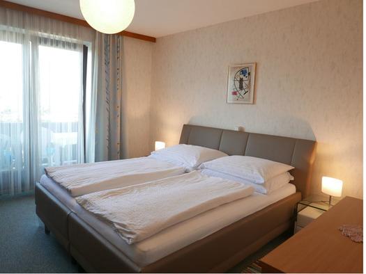 Schlafzimmer mit Doppelbett, Nachtkästchen mit Tischlampen, seitlich eine Balkontür. (© Ramsauer)