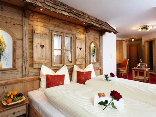 Schlafzimmer mit Doppelbett, auf dem Bett Rosen, Nachtkästchen mit gefüllter Obstschüssel, im Hintergrund Wand verkleidet mit Holz wie eine Hütte, mit Fenster, Dachschindel, im Hintergrund Rollwagen und Sessel. (© Stabauer)