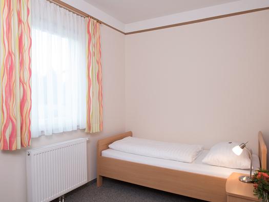 Einzelbett, Nachtkästchen, Tischlampe, seitlich ein Fenster, Heizkörper darunter. (© Taubenberger)