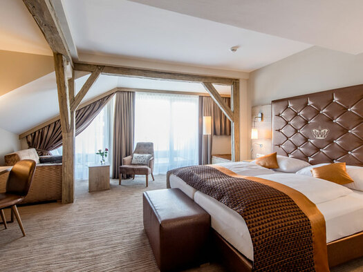 Doppelbett mit Zierkissen, kleiner Schreibtisch mit Sessel und Lampe am Fenster Armsessel kleiner Tisch mit Blumenvase. (© Hotel Krone)