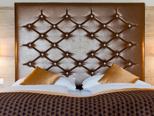 Doppelbett mit Zierkissen und Kopfteil aus Leder, seitlich Leselampen. (© Hotel Krone)