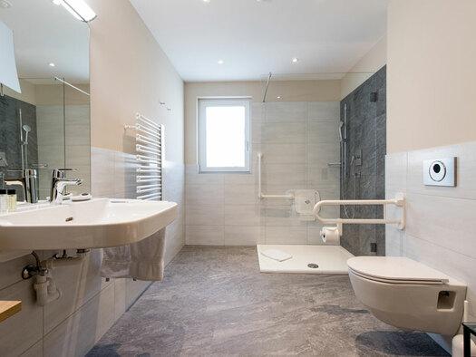 Rollstuhlgerechtes BadezimmerBlick in das Badezimmer, mit Toilette, Dusche im Hintergrund, seitlich ein Waschbecken mit Spiegel, im Hintergrund ein Fenster. (© Hotel Krone)