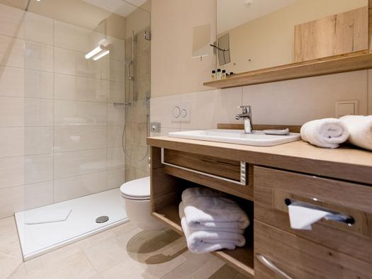 Waschbecken, Spiegel, im Hintergrund eine Dusche. (© Hotel Krone)