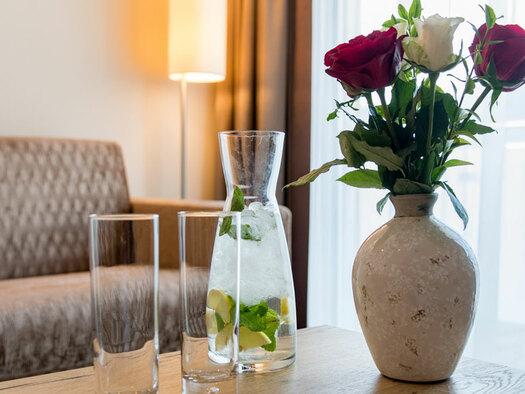 Tisch mit Getränken und Blumenstrauss, Couch mit Stehlampe im Hintergrund. (© Hotel Krone)