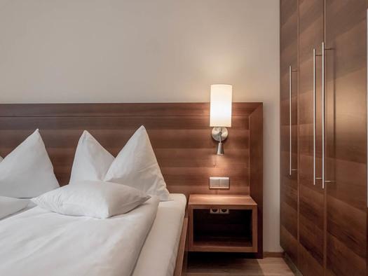 Doppelbett, Lampe, seitlich ein Kleiderschrank. (© Lackner)