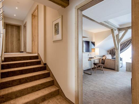 Stiegen, seitlich Blick durch eine offene Tür den in Wohnbereich. (© Hotel Krone)