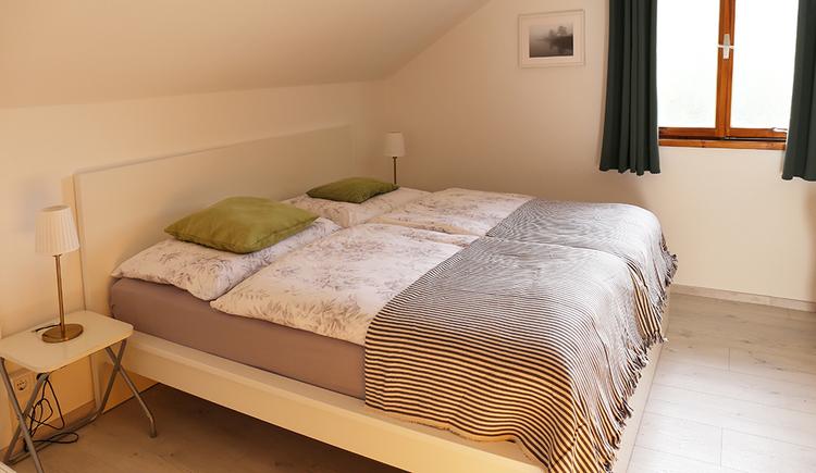 Blick in das Schlafzimmer mit Doppelbett, kleiner Tisch mit einer Lampe,  im Hintergrund ein Fenster