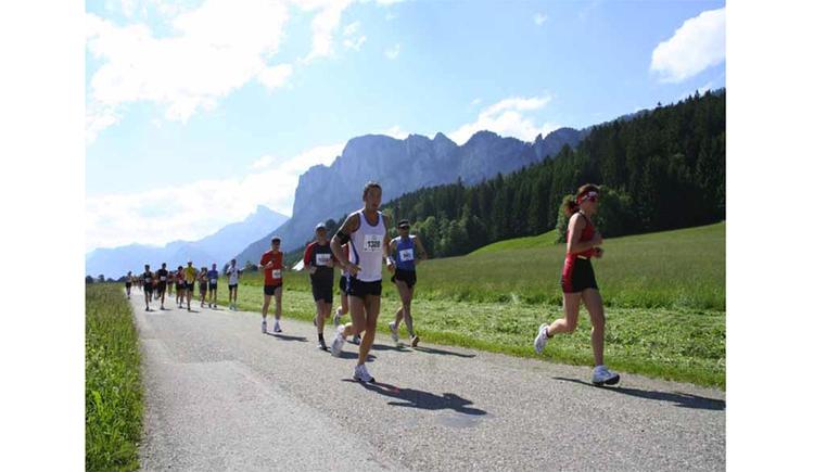 Läufer auf der Straße, im Hintergrund die Landschaft, Wälder und Berge