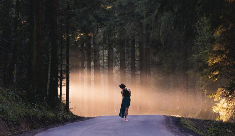 Person steht auf einer Straße im Wald