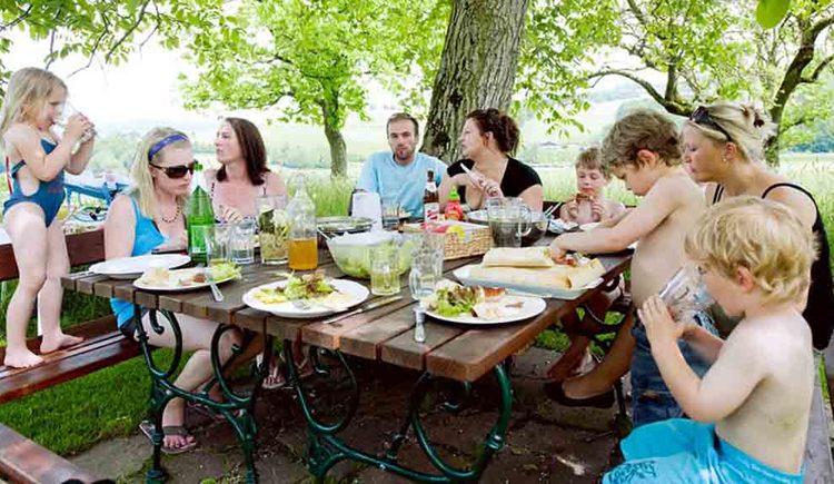 Personen sitzen auf Bänke bei einem gedeckten Jausentisch. (© Gaderer)