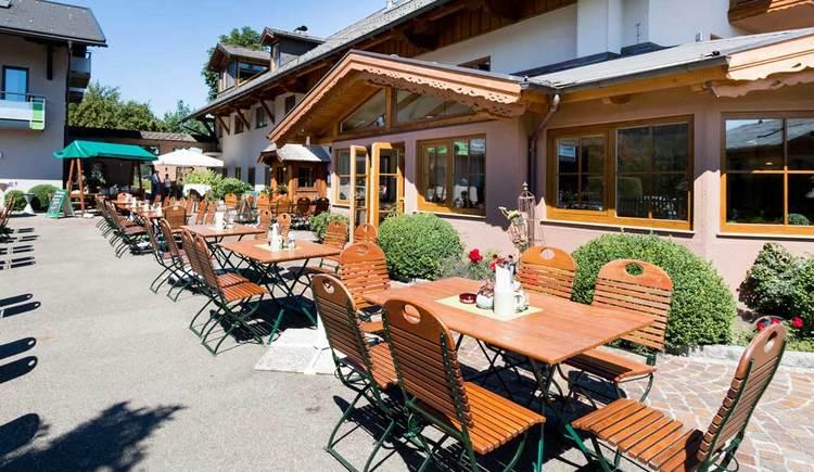 Blick in den Gastgarten, mit einigen Tischen und Stühlen. (© Aichingerwirt)