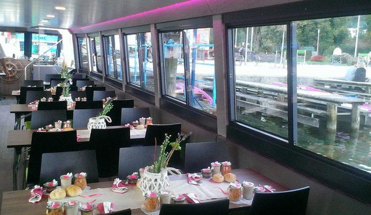 Innenbereich eines Schiffes mit mehreren Tischen und Stühlen, auf den Tischen stehen kleine Snacks und Blumen. (© Mondsee Schifffahrt Hemetsberger)