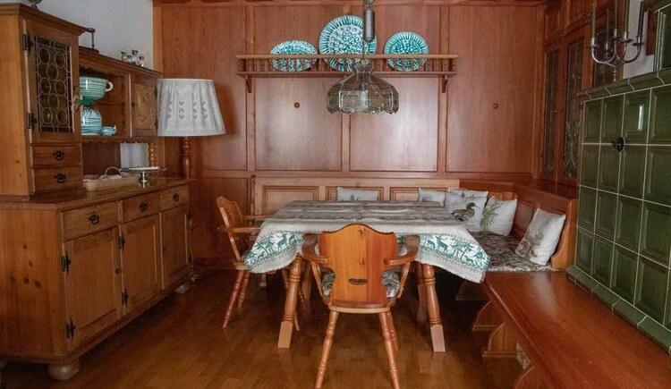 Essecke im Wohnbereich mit Kachelofen in der Butchi-Suite. (© Sommerfrische Apartments)