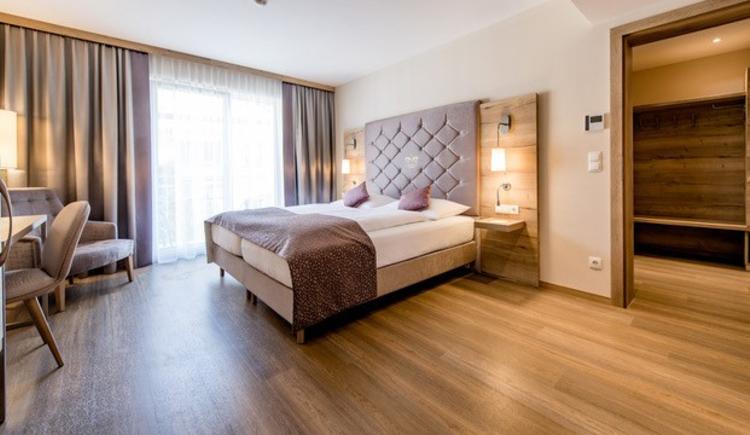 Blick auf das Bett, Sessel, im Hintergrund eine große Balkontür