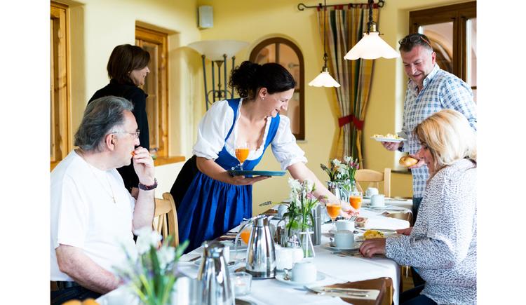 gedeckter Tisch beim Frühstück, Personen sitzen/stehen. (© Ellmauer)