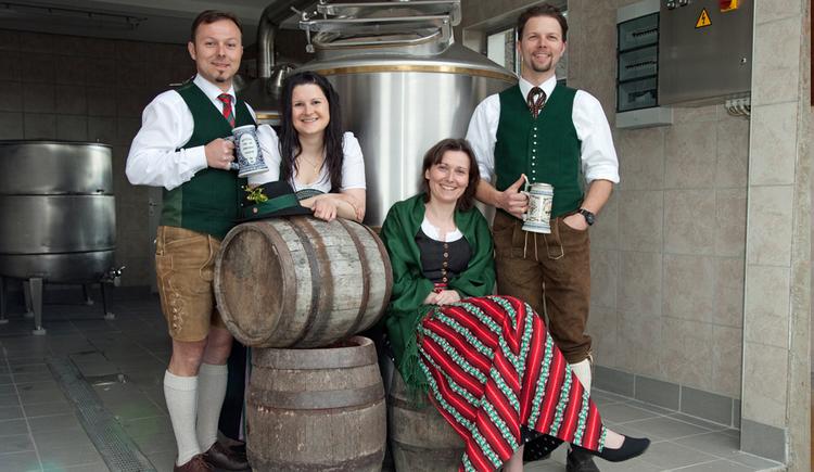 Das Team der Brauere Kaltenböck, 4 Personen mit Brauanlage und Bierfässern im Hintergrund