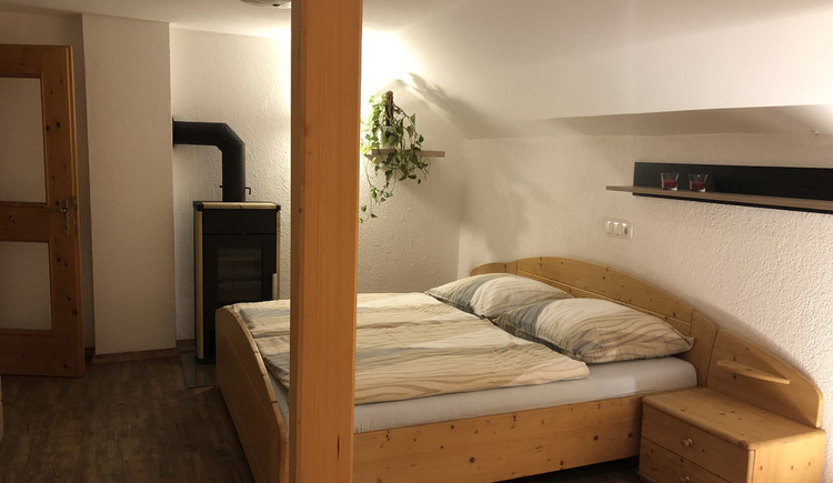 Kuscheliges Doppelbett mit kleinem Ofen zum Heizen.