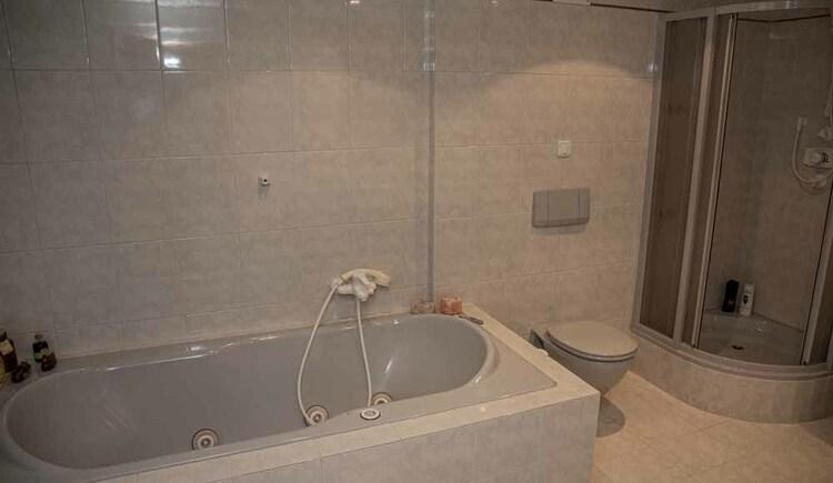 Geräumiges Badezimmer mit Dusche und Whirlpoolbadewanne in der Butchi-Suite Bad Goisern. (© Sommerfrische Apartments)