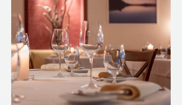 gedeckter Tisch mit Gläser, Servietten, Teller, Besteck, im Hintergrund Bilder. (© Lackner)