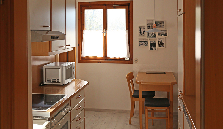 view into the kitchen, table, chairs, window in the background