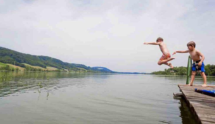 Kinder auf dem Steg, das Andere springt in den See. (© Gaderer)
