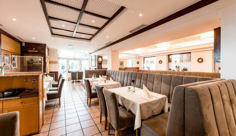 An der Seite Sitzbänke mit Tischen und Stühlen, Tische sind gedeckt. (© Hotel Krone)