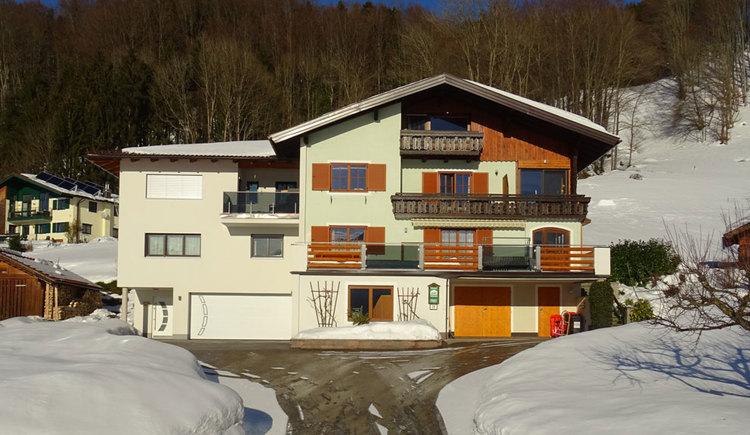 Blick auf das Gästehaus mit Schnee auf den umliegenden Wiesen