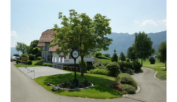 Blick auf das Haus, im Vordergrund eine große Standuhr, Bäume, Wiesen, im Hintergrund seitlich Berge. (© Hotel Villa Drachenwand)