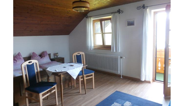 Schlafzimmer mit Doppelbett, Tisch und Stühle, seitlich ein Fenster und eine Balkontür