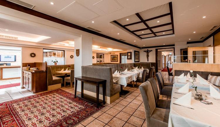 Speisesaal mit vielen Tischen, Stühlen und Bänken. Am Fliesenboden liegt ein großer orientalischer Teppich.