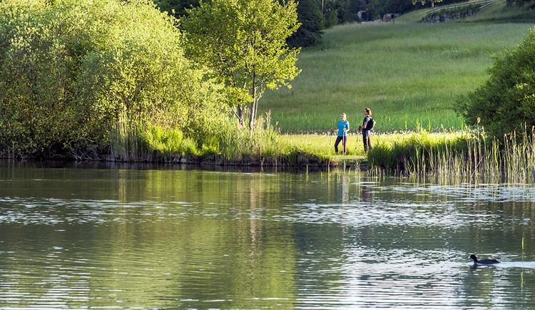 Wanderer stehen am Ufer, im Hintergrund Wiesen und Bäume. (© Valentin Weinhäupl)