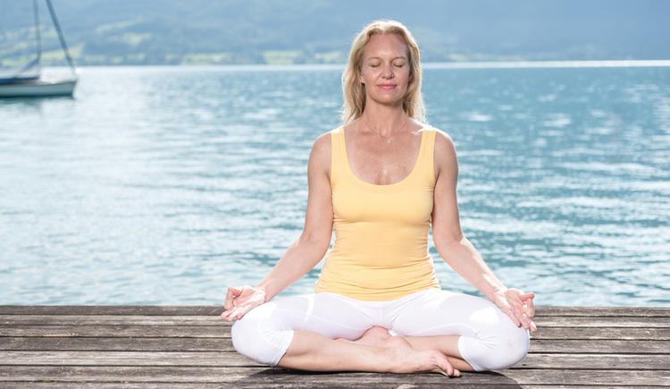 Dame in Yogaposition am Steg, dahinter der See