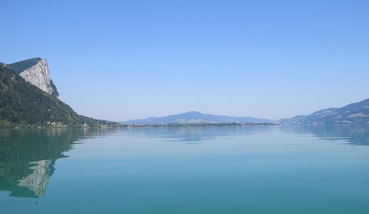 Blick von einem Boot in etwa von der Mitte des Mondsees Richtung Norden. Links dominiert die Drachenwand von einem ungewöhnlichen Blickwinkel, rechts der Mondseeberg. Im Hintergrund ist der Kolomansberg erkennbar. (© www.mondsee.at)