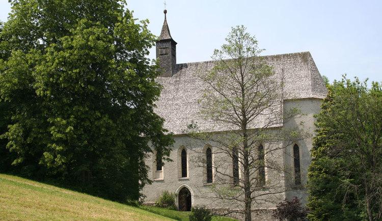 Außenansicht der Konradkirche, im Hintergrund sowie vor der Kirche sind ein paar Bäume und Sträucher. (© www.mondsee.at)
