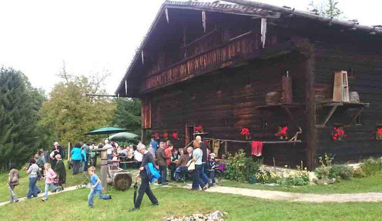 """altes Holzhaus \""""Rauchhaus\"""", im Vordergrund Personen"""