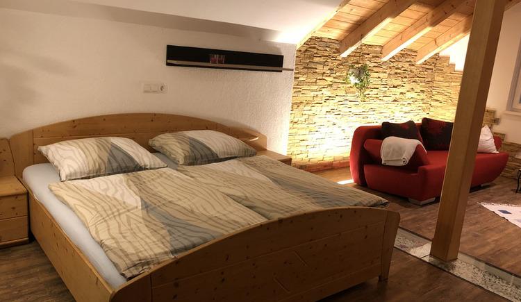 Doppelbett im offenen Wohnraum.