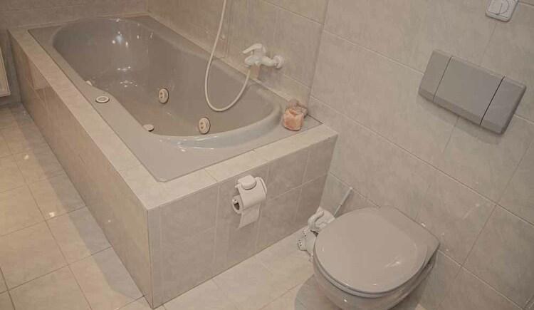 Badezimmer mit Dusche und Whirlpoolbadewanne in der Butchi-Suite Bad Goisern. (© Sommerfrische Apartments)