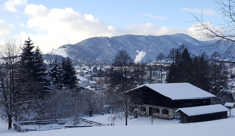 View of the snowy house, in the background trees, mountains. (© Tourismusverband MondSeeLand)