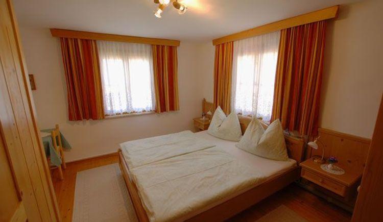 Freundliches Zimmer mit Doppelbett und einem kleinen TV Raum. (© Hedwig Gamsjäger)