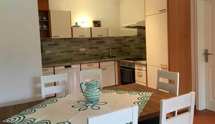 Tisch mit Stühlen im Vordergrund, dahinter ist eine Einbauküche und auf der Seite eine Tür