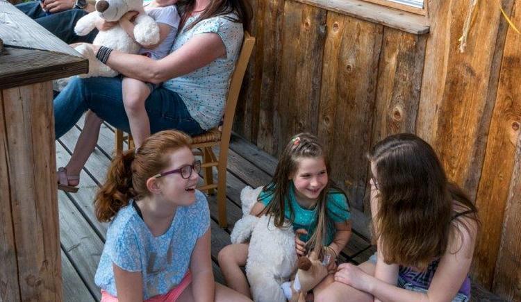 Kinder sitzen am Balkon vom Baumhotel. (© Baumkronenweg Kopfing)