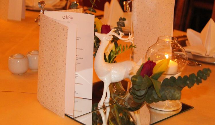Tischdeko mit Menükarte, Blumen, Kerze und weissem Hirsch. (© www.mondsee.at)