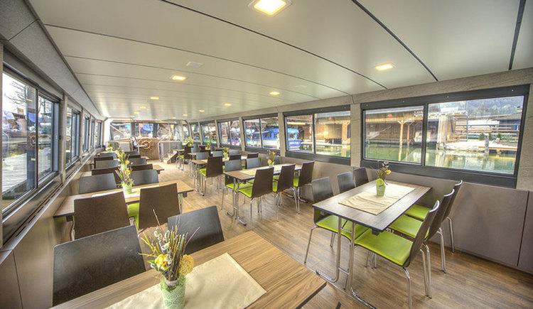 Innenbereich eines Schiffes mit mehreren Tischen und Stühlen. (© Mondsee Schifffahrt Hemetsberger)