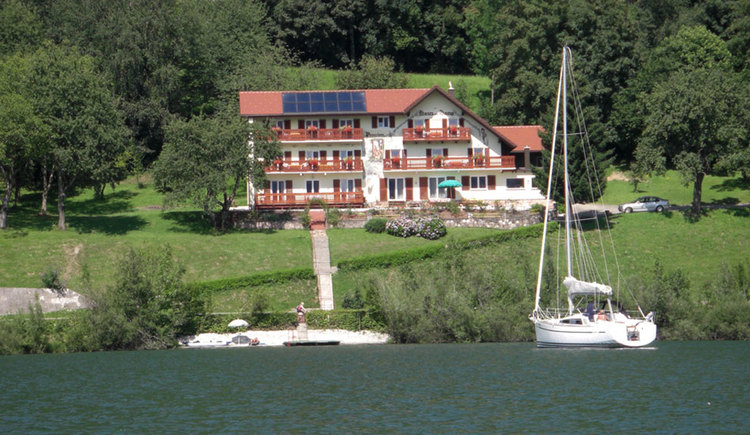 View from the lake to the house whit is rounded from meadow and trees, on the side a sailboat. (© Weber)