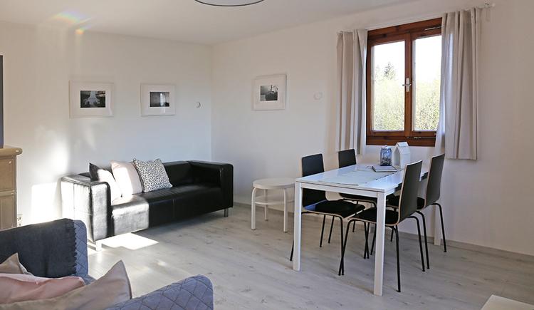 Tisch mit Stühlen, Couch, im Hintergrund ein Fenster