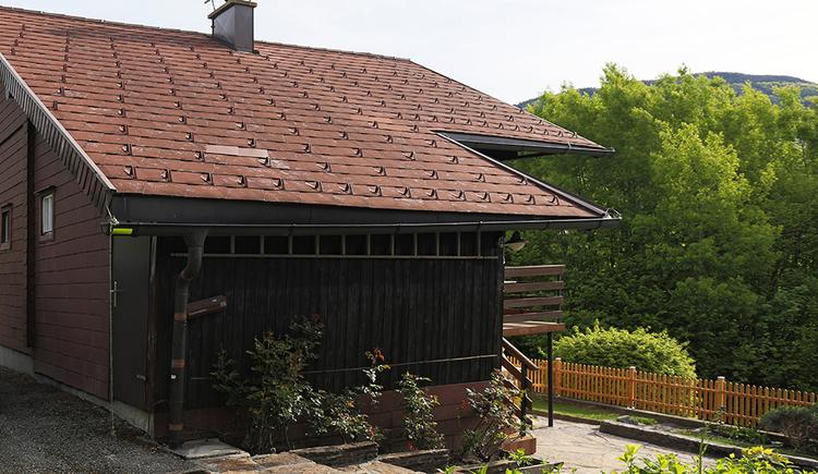 Blick auf das Haus von der Seite, im Vordergrund Bäume