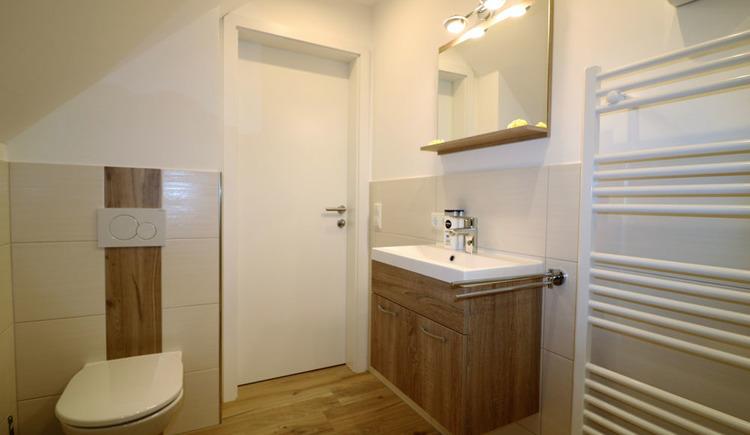 Geräumiges Badezimmer mit Waschbecken, Toilette und Handtuchtrockner